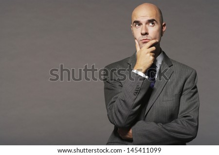 Bald businessman with hand on chin thinking against gray background - stock photo