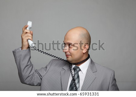 Bald businessman with the handset in hand and wearing a gray suit.
