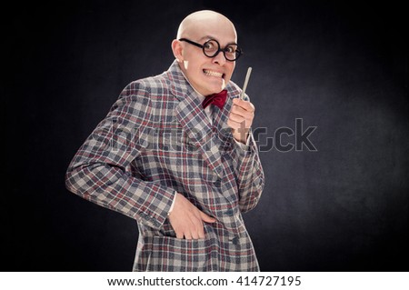 bald caucasian professor or teacher with bow and glasses tie point stick on blackboard with copy space - stock photo