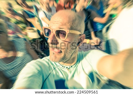 Bald funny man taking a selfie in the crowd with stupid tongue out expression - Travel lifestyle enjoying moment of carefree loneliness - Vintage filtered look - stock photo