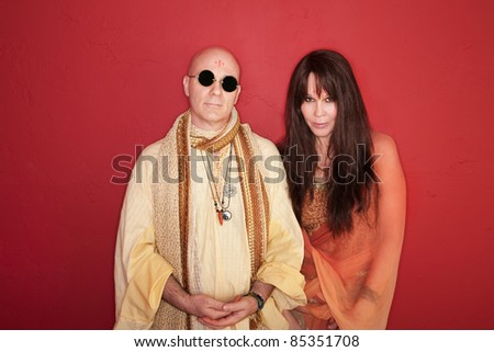 Bald Guru meditates with partner over maroon background - stock photo
