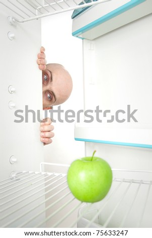 Bald head of young man looking around corner of open refrigerator containing single green apple. - stock photo