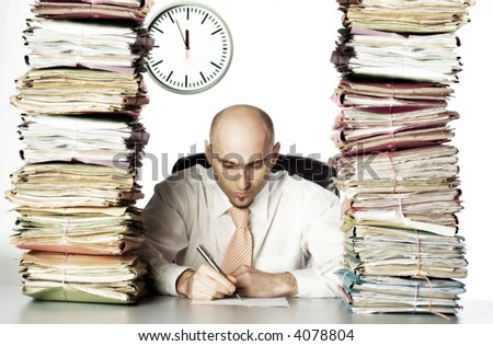 Bald headed businessman surrounded by stacks of files.  Concentrating on paperwork in front of him. Clock is visible in background. - stock photo