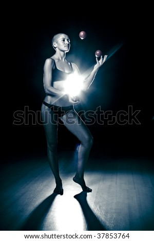 Bald-headed girl juggles on black background.