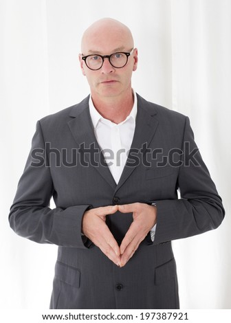 bald-headed man in a suit making gesture with his hands - stock photo