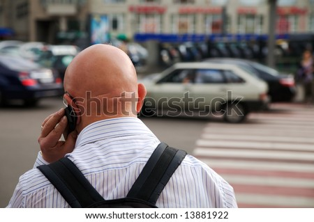 Bald-headed man talking on a cellular phone on the street. A view from the back