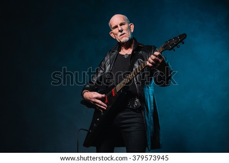 Bald heavy metal senior man with electric guitar in front of dark blue background.