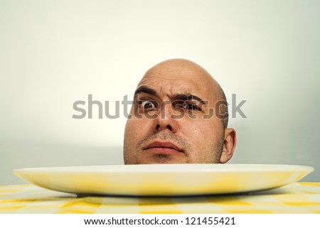 Bald human head with open eyes on a dinner plate