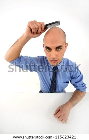 Bald man holding comb - stock photo