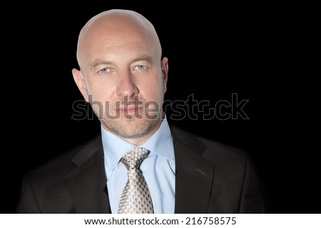 Bald man in a suit and tie on a black background - stock photo