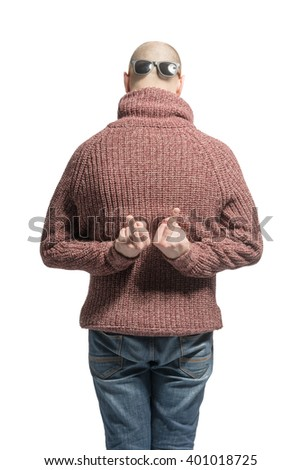 Bald man in a sweater, jeans and sunglasses with his back showing the middle finger. Toned - stock photo