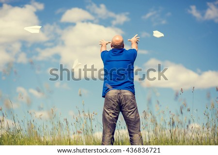 Bald man in blue polo is launching paper planes with a background of blue sky with white clouds. Back view. Image with selective focus and toning.
