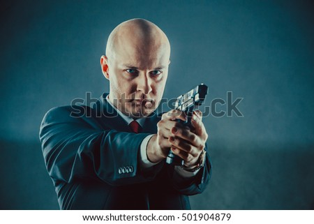 Bald man in business suit with the gun.