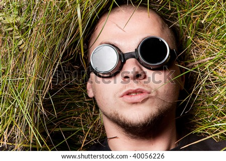 bald man in grass stare to all of you through round glasses, think about it - stock photo