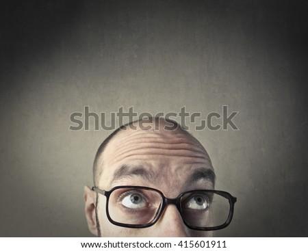 Bald man looking upwards - stock photo