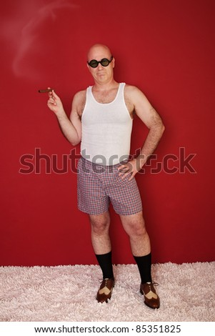 Bald man smokes cigar with hand on hips over maroon background - stock photo