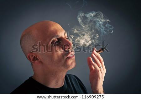 Bald man smoking cigar portrait on dark background. - stock photo