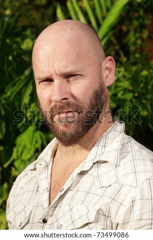 Bald man squinting his eyes - stock photo