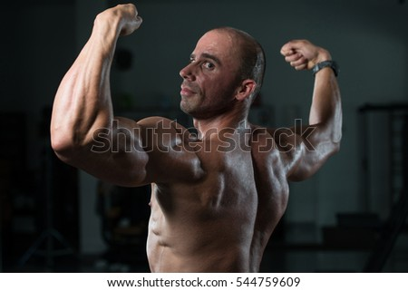 Bald Man Standing Strong In The Gym And Flexing Muscles - Muscular Athletic Bodybuilder Fitness Model Posing After Exercises