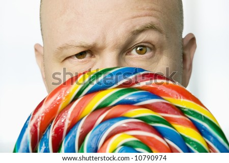 Bald man stares from behind a colorful lollipop - stock photo