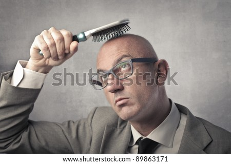 Bald man trying to brush his hair
