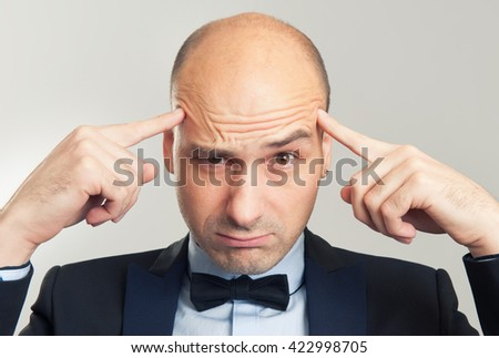 bald man trying to think with his hands on temples - stock photo