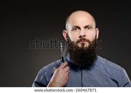 Bald man with a beard holding a pair of scissors - grey background - stock photo