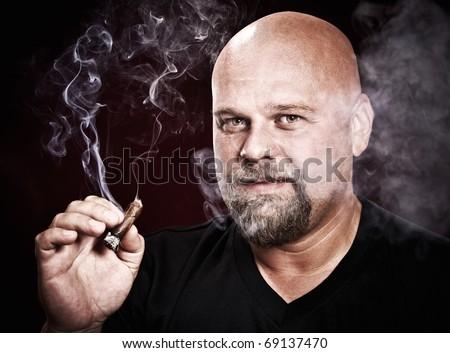 bald man with a beard smokes a cigar - stock photo