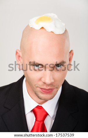 Bald man with fried eggs on top of head looking at camera - stock photo