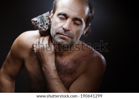 bald man with little cat  on a dark background - stock photo