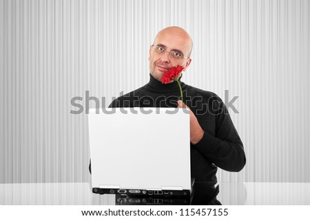 Bald man with red flower in front of a computer