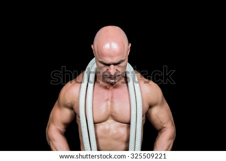 Bald man with rope around neck against black background - stock photo