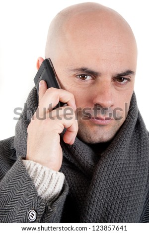 Bald man with tweed coat and scarf on the phone looking at camera. Isolated. - stock photo