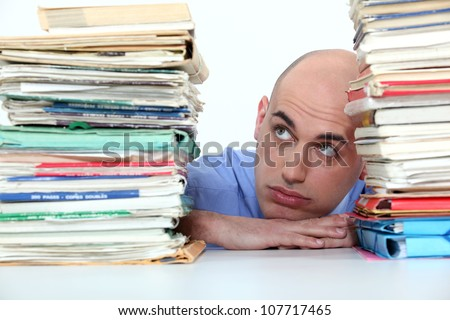 Bald office worker swamped with work - stock photo