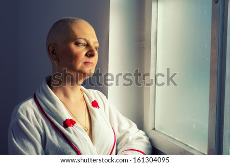 Bald woman suffering from cancer looking through the hospital window. - stock photo