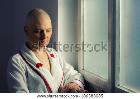 Bald woman suffering from cancer standing in front of the hospital window. - stock photo
