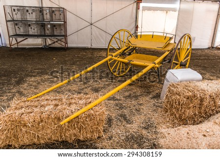 Bales of hay near an old wooden carriage that is empty - stock photo