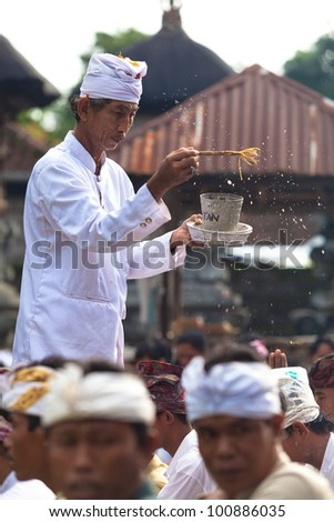 BALI - FEBRUARY 1. Priest blessing worshippers with holy water for Galungan ceremony on February 1, 2012 in Bali, Indonesia. Galungan's a Balinese holiday occuring every 210 days lasting 10 days.