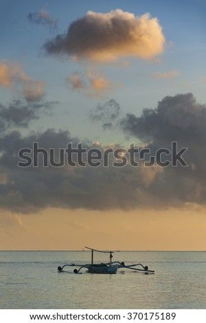 Bali, Indonesia. A small fishing boat, called a jukung, works the coastline in the area known as Amed in east Bali, Indonesia during a lovely sunrise.