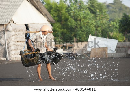 Bali Indonesia Apr 3, 2016 : Traditional salt farmer pouring sea water into black sand as a part of the process of producing traditional salt in Kusamba Beach Bali Indonesia.