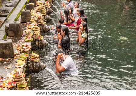 Bali, Indonesia, April 21,2010 : Balinese people praying at holy spring water at  Pura Tirtha Empul temple during religious ceremony  in Tampak Siring, Bali, Indonesia. - stock photo