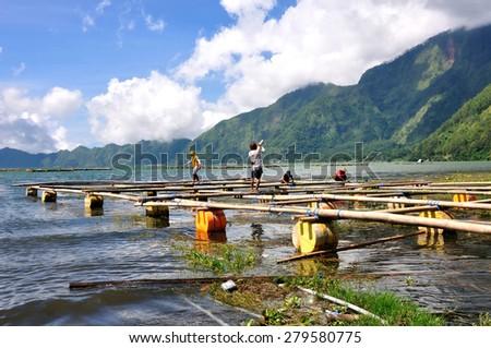 BALI,INDONESIA - April 16,2015: Fishermans making their float fishing village in Lake Batur. - stock photo