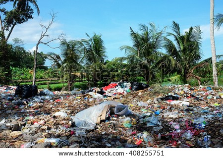 BALI, INDONESIA - APRIL 10: Household garbage and plastic bags contaminate rice fields and agricultural farmland at an illegal landfill site on April 10, 2016 in Ubud, Bali, Indonesia. - stock photo