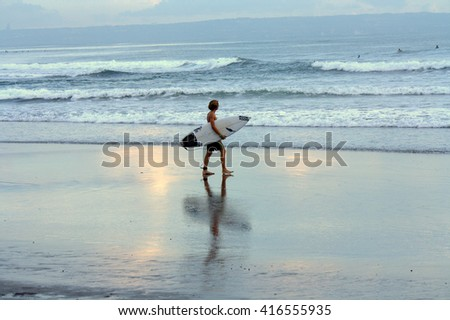 Bali, Indonesia - February 20, 2016 :  surfer walking with a surfing board sunset at Echo Beach.Bali is one of the best surf destinations in the world for beginners up to pros.