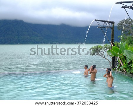 BALI, INDONESIA - FEBRUARY 3, 2016: Unknown people bathing in a hot springs infinity pool beside Batur lake, Kintamani, Bali, Indonesia. - stock photo
