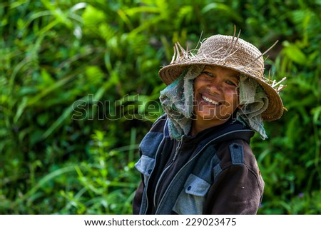 Bali, Indonesia - January, 12 - 2014 : Balinese farmer women smiling with a straw hat on her head