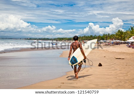 BALI, INDONESIA - JANUARY 13: Unidentified young man with surf board on January 13, 2012. Dreamland beach, Bali, Indonesia. The Dreamland is one of the most popular surfing areas of Bali. - stock photo
