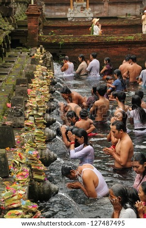 BALI, INDONESIA - JULY 15: Balinese Hindu families come to the sacred springs of Tirta Empul in Bali, Indonesia to pray and cleanse their soul on July 15, 2012. Worshipers are drawn to Tirta Empul for its curative properties.