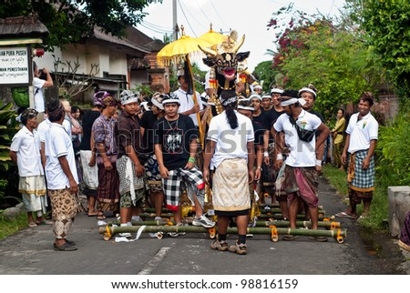 BALI, INDONESIA, JULY 14: unidentified Balinese people preparing for the parade during the cremation ceremony in Penestanan, Bali on July 14th 2010. - stock photo