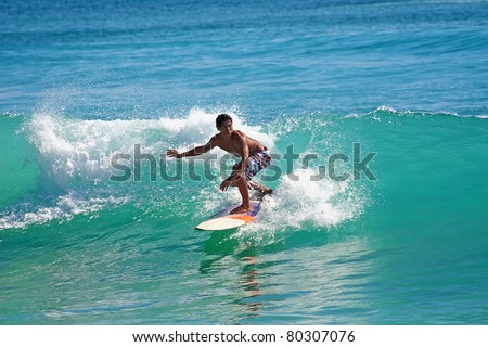 BALI, INDONESIA - JULY 27: Unidentified young man surfing the waves on Dreamland beach on July 27, 2010 in Bali, Indonesia. The Dreamland is one of the most popular surfing areas of Bali. - stock photo